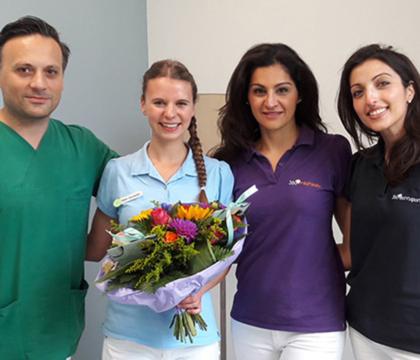Zahnmedizinische Fachangestellte Malin mit Blumenstrauss und Team